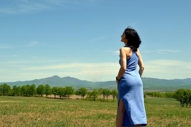 Glimlachende donkerbruine vrouw die lange blauwe kleding draagt