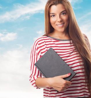 Glimlachende donkerbruine vrouw die zwarte notebook