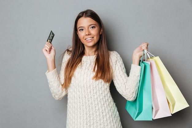 Glimlachende donkerbruine vrouw in de pakketten en de creditcard van de sweaterholding