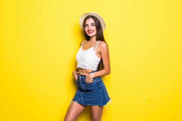 Glimlachende donkerbruine vrouw in sweater het stellen met gekruiste wapens over gele muur