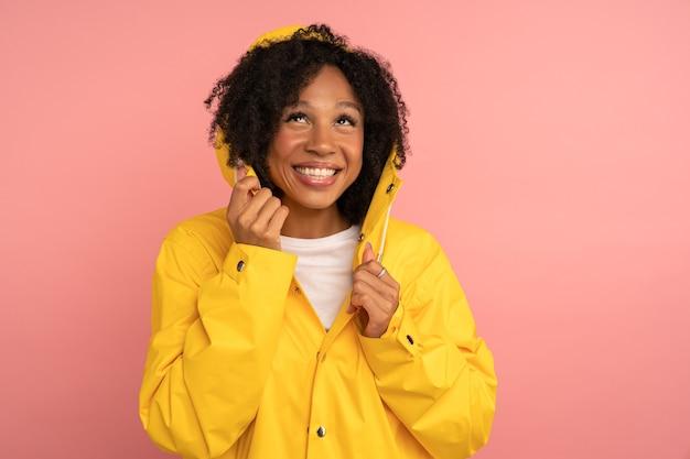 Glimlachende donkere gekrulde vrouw in gele regenjas met capuchon heeft een goed humeur