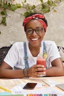 Glimlachende donkere modieuze vrouw met tevreden uitdrukking, geniet van verse smoothie, werkt met documentatie