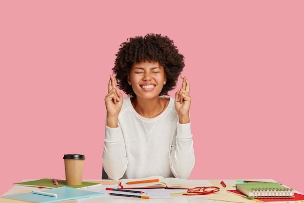 Glimlachende donkere vrouwelijke wetenschapper houdt de vingers gekruist, poseert op het bureaublad, hoopt op succesvol onderzoek
