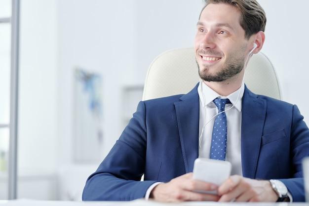 Glimlachende dromerige jonge zakenman die van muziek in oortelefoons geniet terwijl hij aan nieuw projectidee denkt