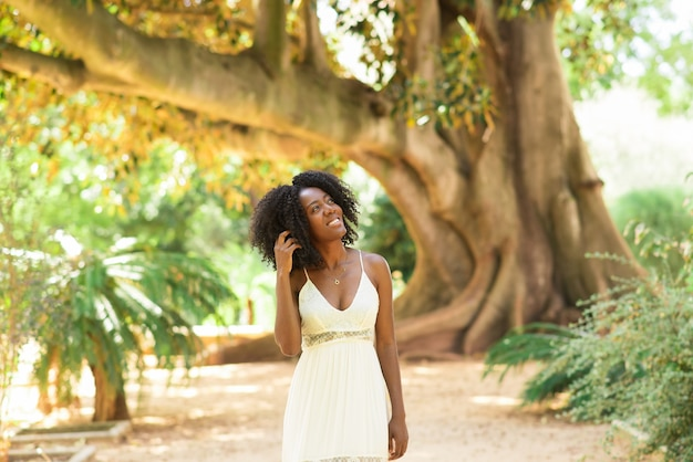 Glimlachende dromerige zwarte vrouw wandelen in park