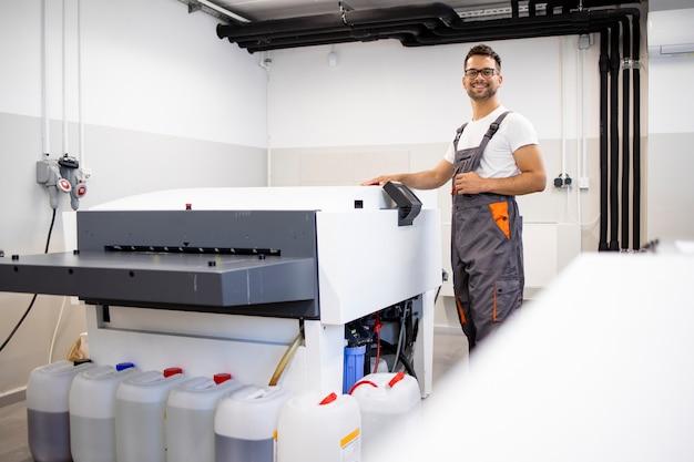 Glimlachende drukker die de computer bedient om de machine in de drukkerij te borduren.