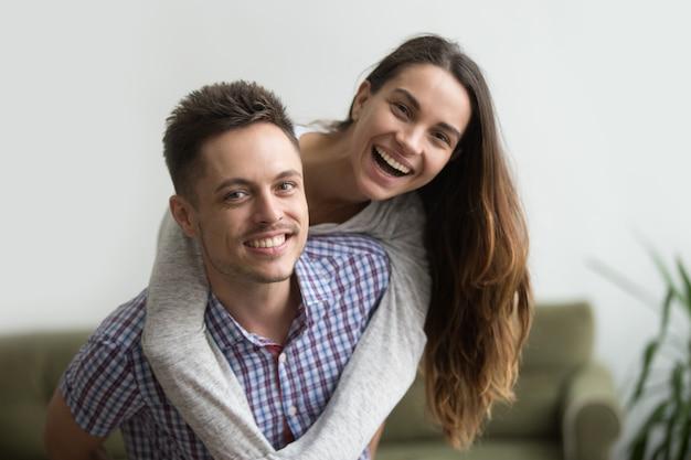 Glimlachende echtgenoot die vrolijke vrouw thuis vervoeren per kangoeroewagen, gelukkig paarportret