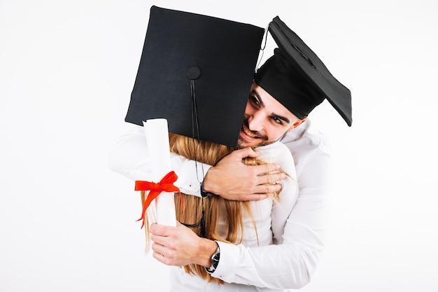 Glimlachende een diploma behalende man die vrouw omhelst