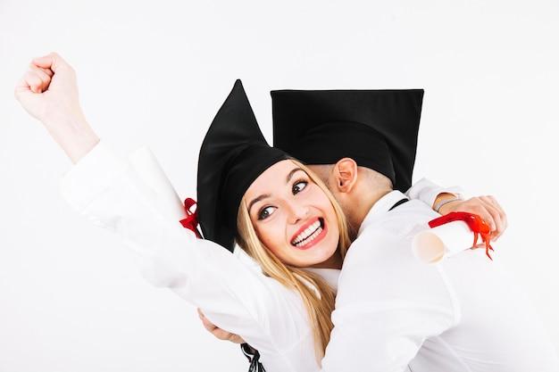 Glimlachende een diploma behalende vrouw die met vriend omhelst
