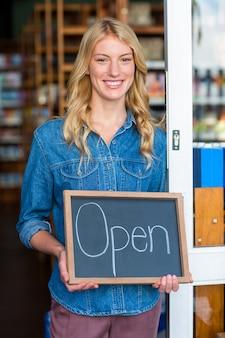 Glimlachende eigenaar die open uithangbord in supermarkt houden