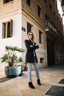 Glimlachende elegante jonge vrouw met zonnebril die dichtbij op straat voortbouwen