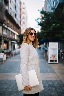 Glimlachende elegante jonge vrouw met zonnebril en laptop op straat