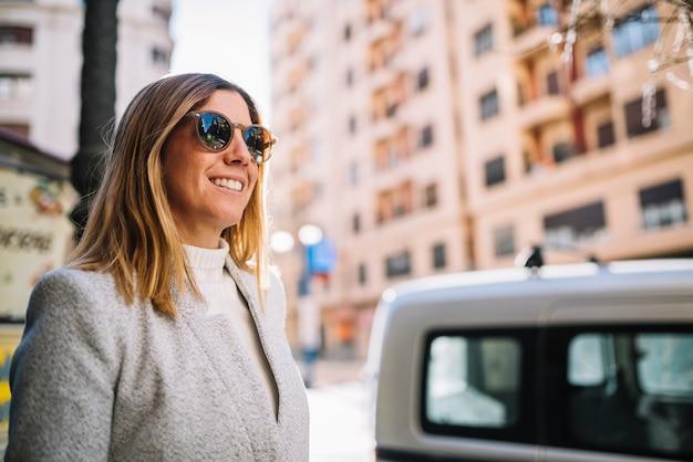 Glimlachende elegante jonge vrouw met zonnebril op straat dichtbij auto