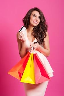 Glimlachende elegante vrouwelijke shopaholic op roze