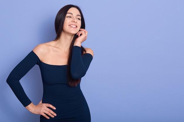 Glimlachende elegantievrouw die donkerblauwe en kleding draagt die zich weg bevindt kijkt. het mooie donkerbruine wijfje houdt één hand op heup en een ander dichtbij gezicht, glimlachend meisje, kopieer ruimte vijand adverisment of bevordering.