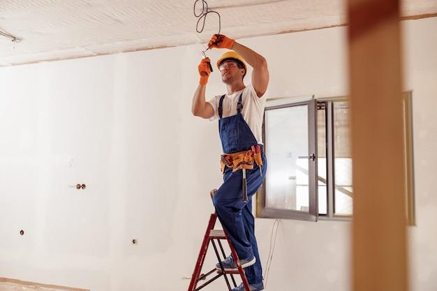 Glimlachende elektricien die elektrische kabel op plafond bevestigt