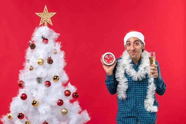 Glimlachende emotionele jonge kerel met de hoed van de kerstman en het opheffen van een glas wijn en het houden van klok die zich dichtbij kerstboom op rood bevindt