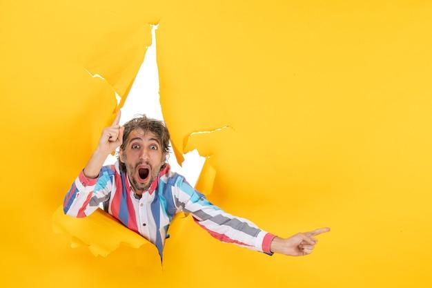 Glimlachende en emotionele jongeman poseert in een gescheurde gele achtergrond van een papieren gat die naar boven wijst en iets aan de linkerkant