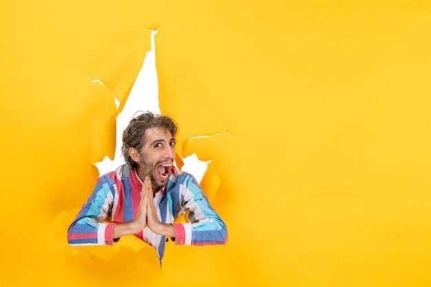 Glimlachende en emotionele jongeman poseert in een gescheurde gele papieren gatachtergrond en maakt een dankgebaar