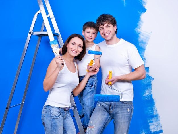 Glimlachende en gelukkige familie met verfborstels die renovatie doen - binnenshuis