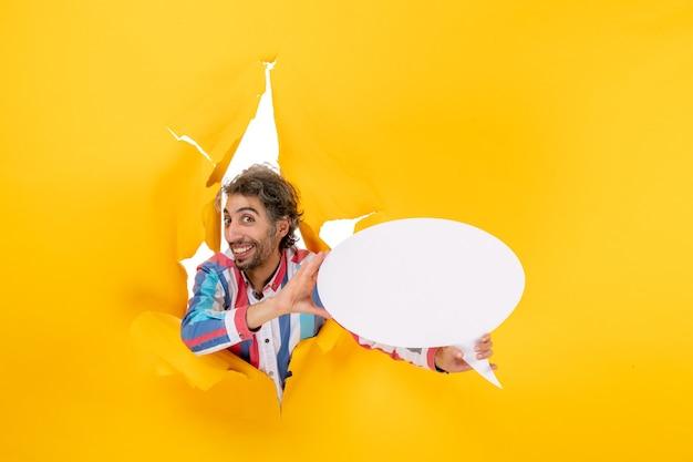 Glimlachende en gelukkige jonge kerel die een witte pagina aanwijst met vrije ruimte in een gescheurd gat in geel papier