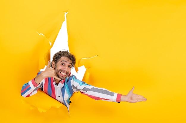 Glimlachende en gelukkige jonge man poseert in een gescheurde gele papieren gatachtergrond die iets wijst en me een gebaar maakt