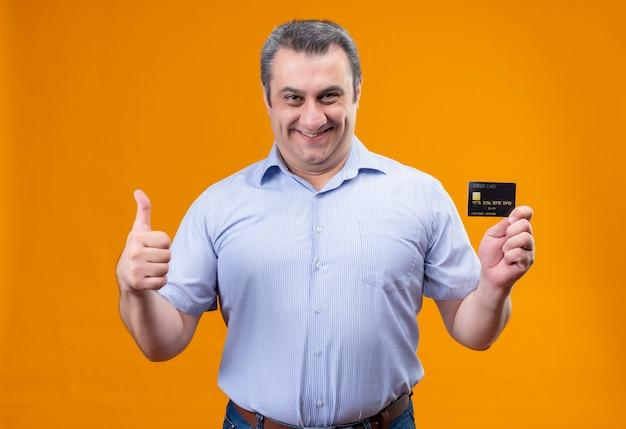 Glimlachende en positieve man van middelbare leeftijd in blauw gestreept overhemd met creditcard terwijl gebaren duimen omhoog op een oranje achtergrond