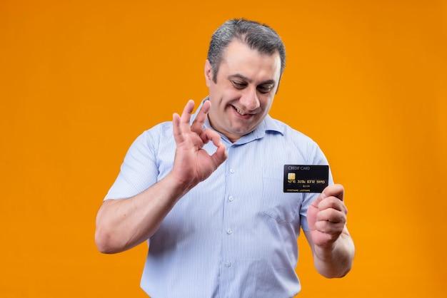 Glimlachende en positieve man van middelbare leeftijd in blauw gestreept shirt kijken naar creditcard terwijl ok handteken op een oranje achtergrond wordt weergegeven