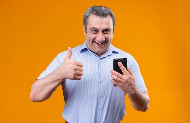 Glimlachende en positieve man van middelbare leeftijd met blauwe gestripte shirt met mobiele telefoon en duimen opdagen terwijl staande op een oranje achtergrond
