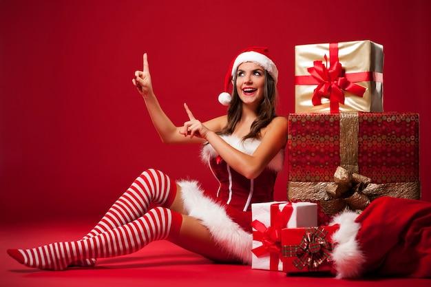 Glimlachende en sexy kerstmanvrouw die bij exemplaarruimte tonen