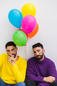 Glimlachende en vermoeide homosexuelen die met ballons zitten