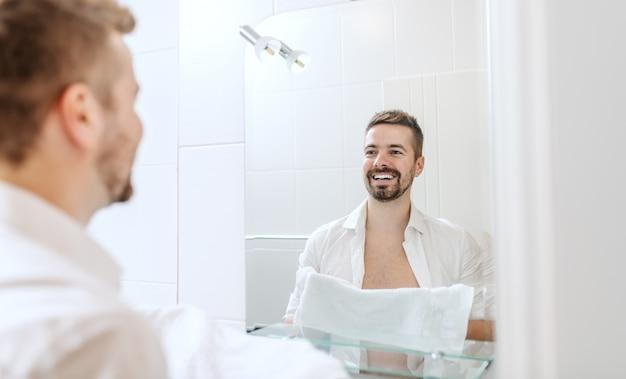 Glimlachende en vrolijke zakenman met knoop overhemd en handdoek in zijn handen die zijn gezicht wassen terwijl status voor spiegel in badkamers.