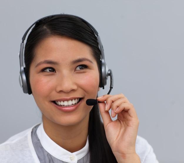 Glimlachende etnische klantendienst die op een hoofdtelefoon spreekt