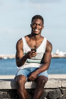 Glimlachende etnische man met smartphone op dijk