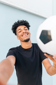 Glimlachende etnische mens die met voetbal camera bekijkt