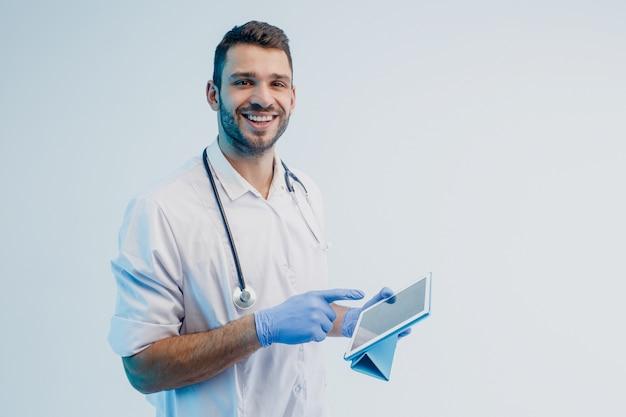 Glimlachende europese mannelijke arts die digitale tablet gebruikt. jonge, bebaarde man met een stethoscoop die een witte jas draagt met latexhandschoenen. geïsoleerd op een grijze achtergrond met turkoois licht. studio opname. ruimte kopiëren.