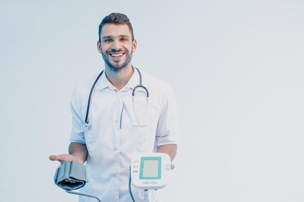 Glimlachende europese mannelijke arts die digitale tonometer toont. jonge, bebaarde man met een stethoscoop die een witte jas draagt. geïsoleerd op een grijze achtergrond met turkoois licht. studio opname. ruimte kopiëren