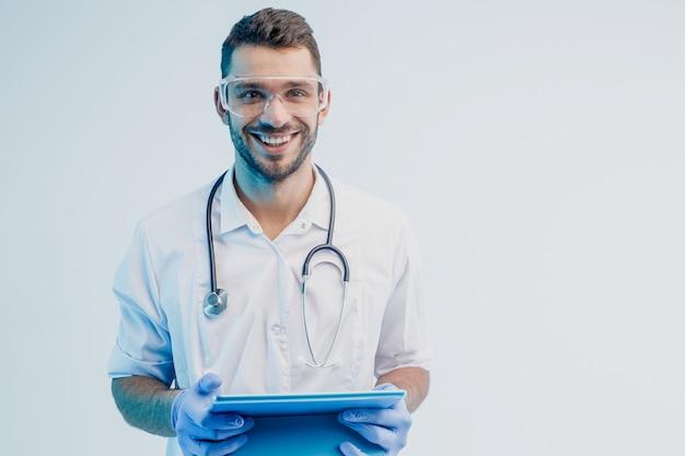 Glimlachende europese mannelijke arts met digitale tablet. jonge, bebaarde man met stethoscoop met witte jas, bril en latexhandschoenen. grijze achtergrond met turkoois licht. studio opname. ruimte kopiëren.