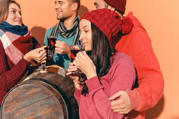 Glimlachende europese mannen en vrouwen tijdens feestfotoshoot. jongens die zich voordeed als vrienden op studio fest met wijnglazen met warme glühwein op voorgrond.