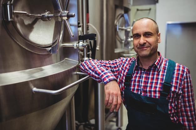 Glimlachende fabrikant die zich in brouwerij bevindt