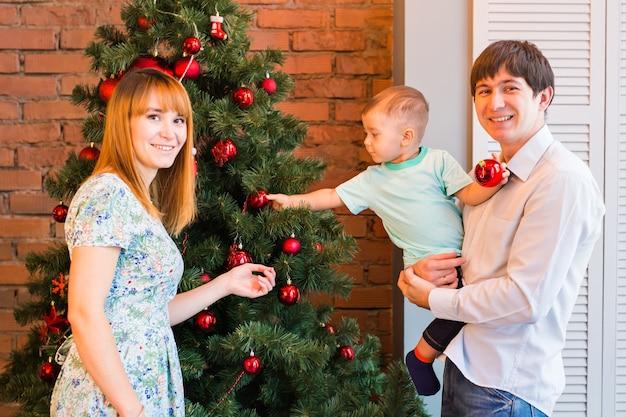 Glimlachende familie die een kerstboom in de woonkamer verfraait