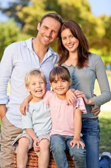 Glimlachende familie die in het park picknicken