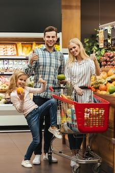 Glimlachende familie die kruidenierswinkels kiest