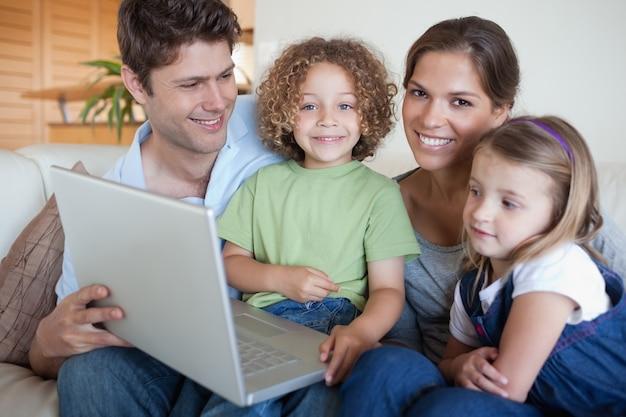 Glimlachende familie die laptop met behulp van