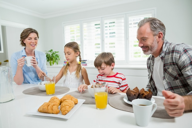 Glimlachende familie die ontbijt in de keuken heeft