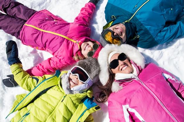 Glimlachende familie die op sneeuw ligt
