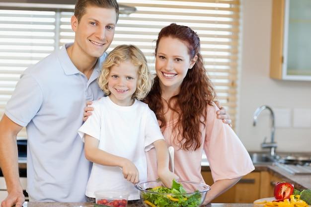 Glimlachende familie die salade samen voorbereiden