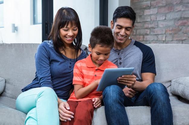 Glimlachende familie die tablet op de bank gebruiken