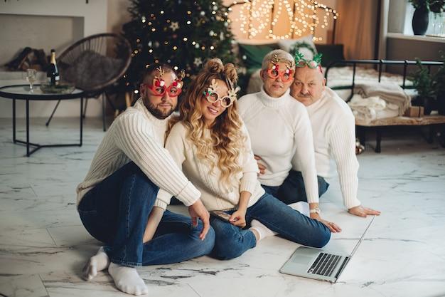 Glimlachende familie die witte truien draagt en op vloer met kerstboom op de achtergrond zit