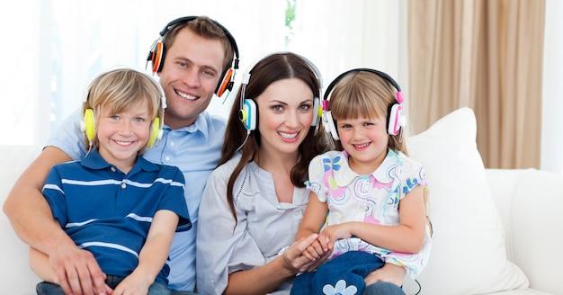 Glimlachende familie het luisteren muziek met hoofdtelefoons